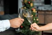Fotografia immagine potata della coppia celebra il Natale e tintinnio di champagne glasse a casa