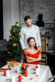 pohledný muž objímá ramena přítelkyně sedí u stolu servírované na Vánoce doma