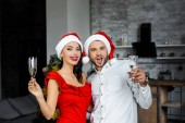 Fotografie excited couple in christmas hats celebrating and having fun with champagne glasses at home