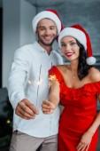 szelektív összpontosít, a fiatal pár karácsonyi kalap gazdaság ragyog otthon