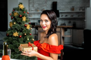 beautiful young woman holding gift box near christmas tree at home