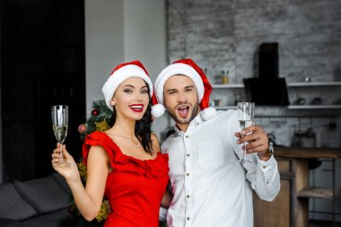 excited couple in christmas hats celebrating and having fun with champagne glasses at home