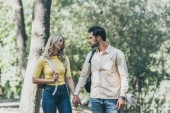 Fotografie portrait of young couple with backpacks holding hands in park