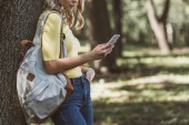 partial view of woman with backpack on shoulder using smartphone in forest