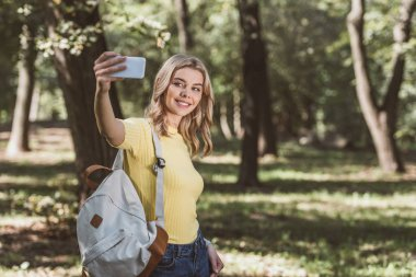 Portrait of smiling woman with backpack taking selfie on smartphone in park stock vector