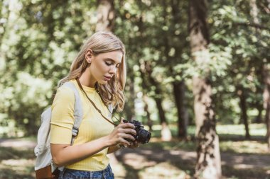 side view of young tourist with photo camera and backpack in park