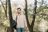 a hátizsák parkban smartphone beszélő fiatalember portréja