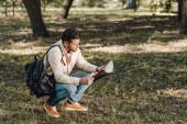 boční pohled na turisty s mapou a batoh v parku