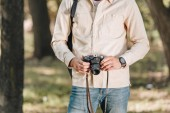 Photo cropped shot of man holding photo camera in hands in park