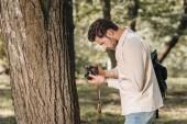 Fotografie boční pohled na mladé cestovatele s fotoaparátem v parku