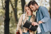 Fotografie portrait of couple of tourists looking for destination on map in park