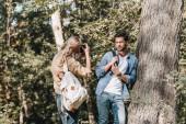Fotografie woman taking picture of stylish boyfriend in autumn park