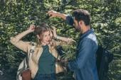 mladý muž pomáhá přítelkyně dostat z větve stromu v parku