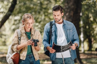 portrait of couple of tourists with photo camera and map in park