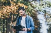 Fotografia Ritratto di giovane viaggiatore concentrato con mappa nella sosta di autunno