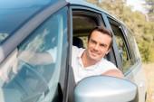 šťastný muž, při řízení auta v poli při pohledu z okna