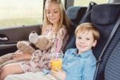 Fotografie entzückende kleine Kinder mit Teddybär und Orangensaft im Plastikbecher im Auto sitzen
