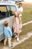 Fotografie entzückende kleine Kinder stehen in der Nähe von Auto, während ihr Vater Eröffnung Stamm im Feld während der Reise