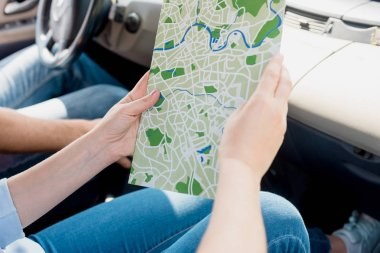 cropped shot of woman holding map while travelling by car