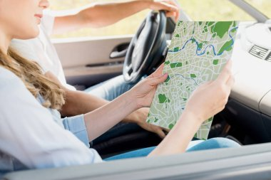 Cropped shot of woman holding map while travelling by car with husband stock vector