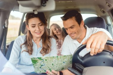 beautiful family looking at map together during car trip