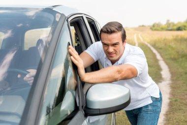 handsome man pushing his broken car in field