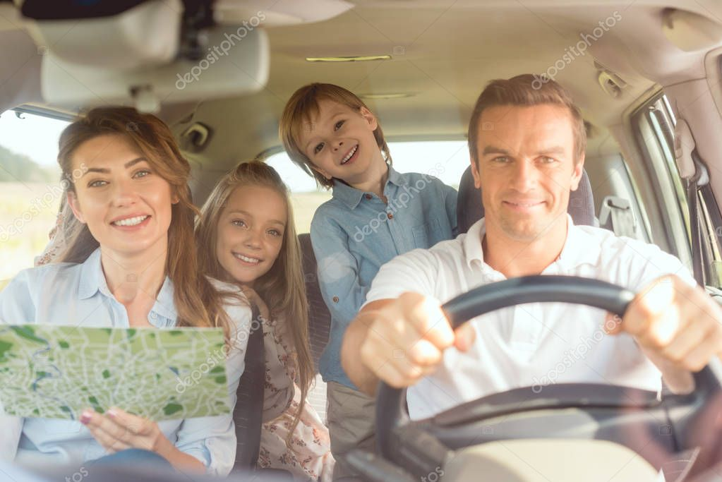 happy young family looking at camera while travelling by car
