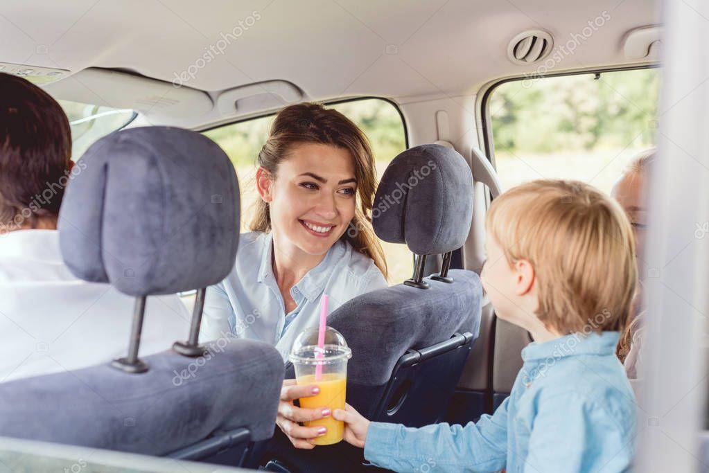 woman giving orange juice to son during car trip