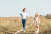 šťastný matka a dcera, drželi se za ruce a společně chodit v poli