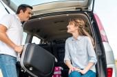 poggyász csomagolás autó törzs, miközben a barátnője nézett rá boldog felnőtt ember