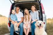 Fotografia bella giovane famiglia con il cane da riporto seduto nel bagagliaio e che guarda lobbiettivo nel campo