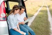 mosolygós felnőtt pár autó törzs ül és nézi megjelenítése, miközben autós utazás