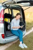 atraktivní pro dospělé žena sedí v kufru auta a při pohledu na mapu v poli