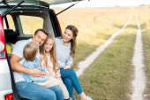 Fotografie beautiful young family spending time together in field while having car trip