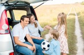 young family spending time together in field while having car trip