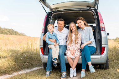 Happy young family sitting in car trunk and looking at camera in field stock vector
