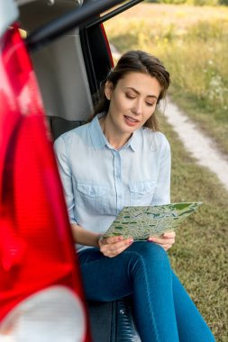 Happy adult woman sitting in car trunk and looking at map in field stock vector