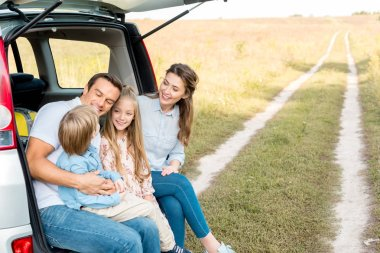 Beautiful young family spending time together in field while having car trip stock vector
