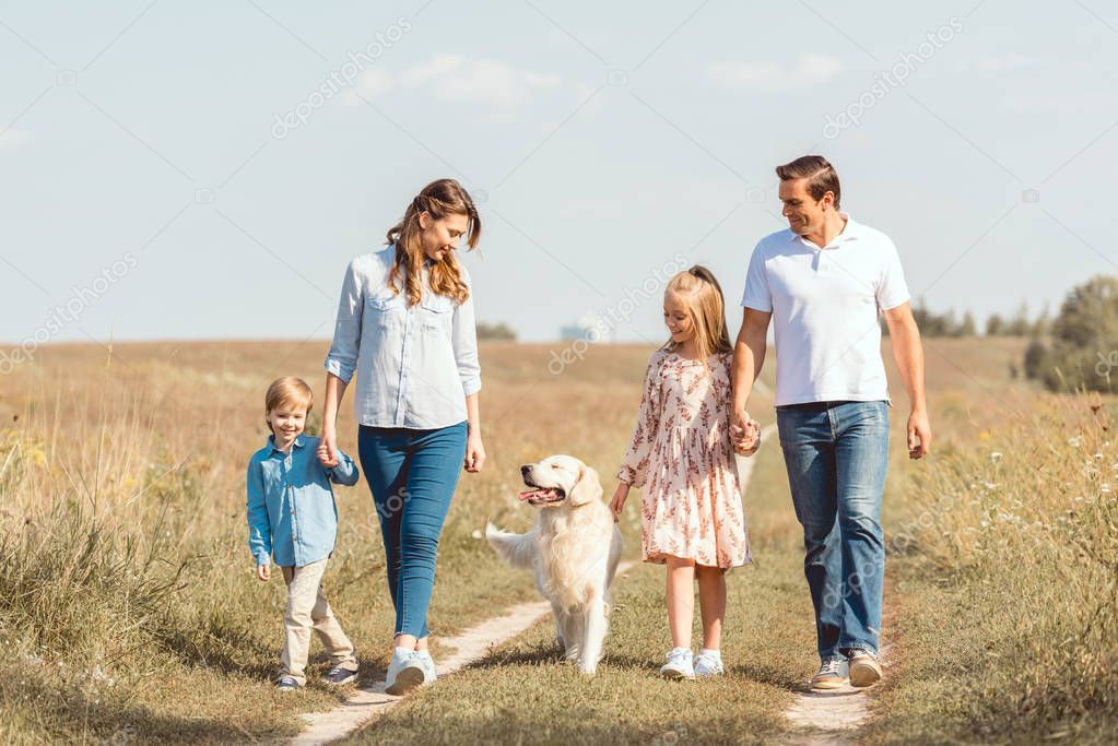 happy young family with retriever dog spending time together in field