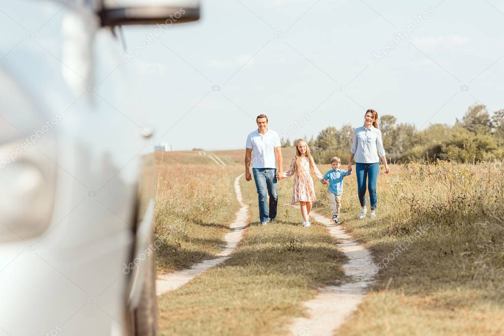 beautiful young family holding hands and walking to car by field