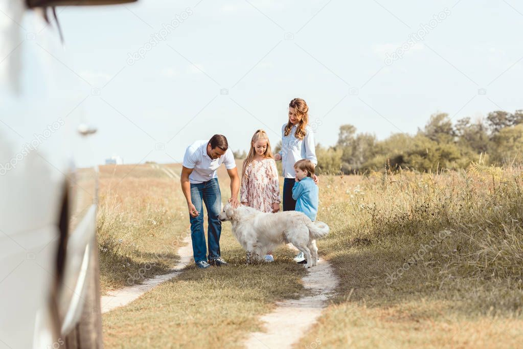 beautiful young family with retriever dog spending time together in field during car trip