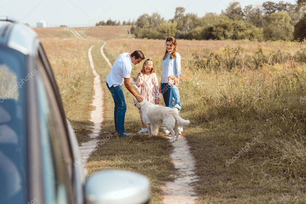 happy young family with retriever dog spending time together in field during car trip