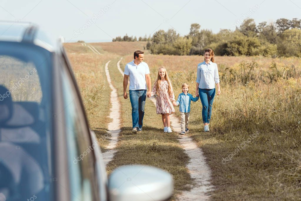 happy young family holding hands and walking to car by field