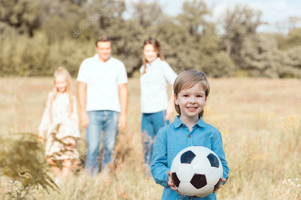 happy little kid holding ball while his family standing blurred on background in field