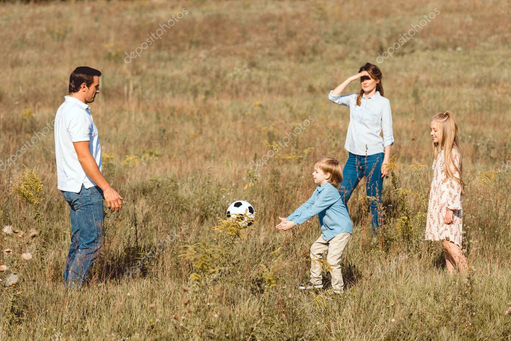 beautiful young family playing football together in nature