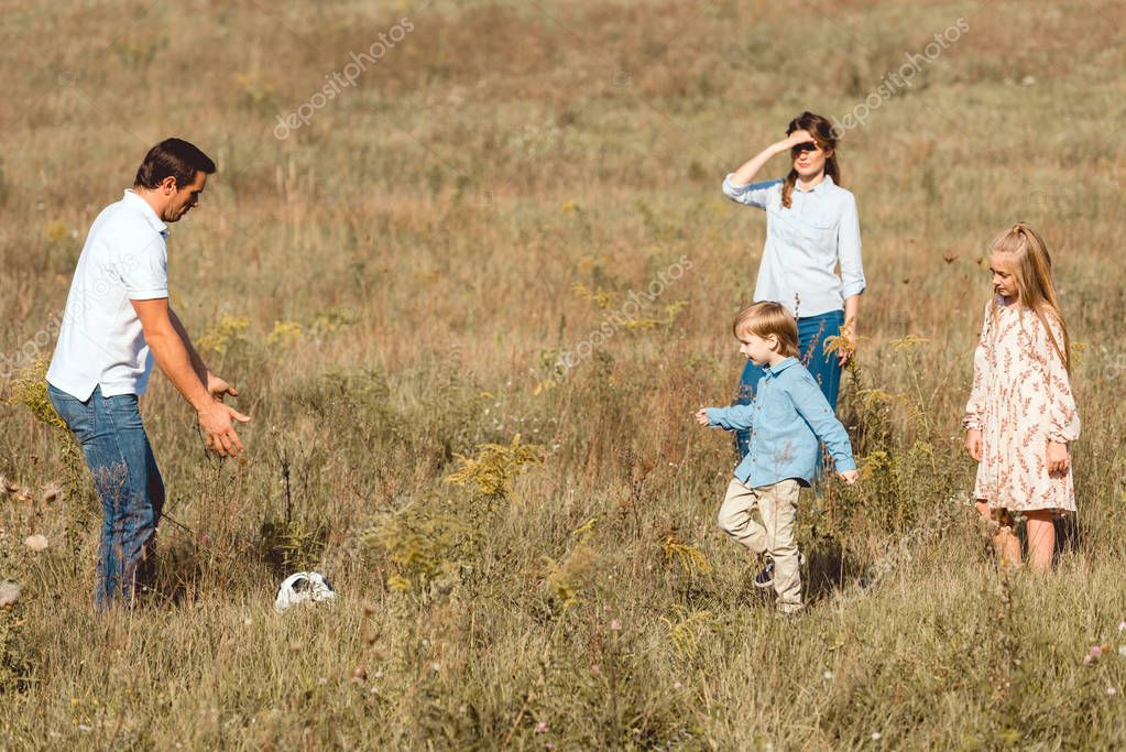 happy young family playing football together in nature