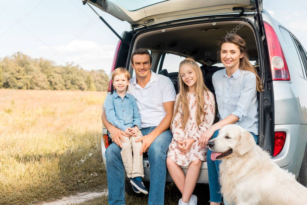 smiling young family with retriever dog sitting in car trunk and looking at camera in field