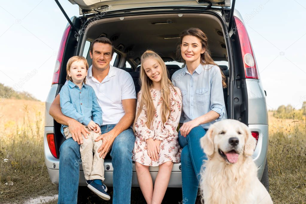 beautiful young family with retriever dog sitting in car trunk and looking at camera in field