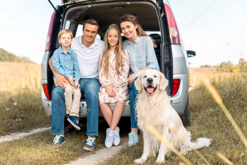happy young family with retriever dog sitting in car trunk and looking at camera in field