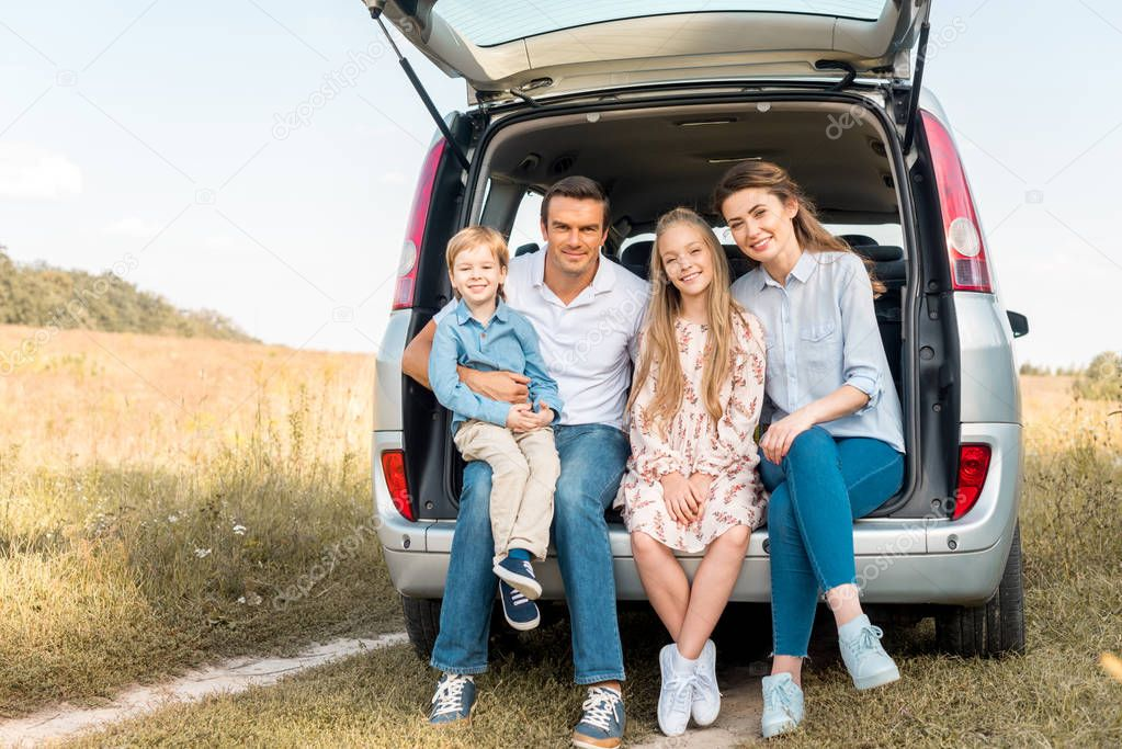 happy young family sitting in car trunk and looking at camera in field